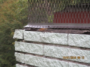 Damaged chimney cap with damaged brick and mortar.